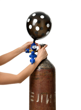 Hands inflate black dotted balloon use Helium Tank with Economy Regulator Fill Valve for Latex Balloons isolated on white background Foto de archivo