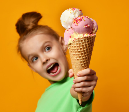 Pretty baby girl kid hold in hand banana and strawberry ice cream in waffles coneon yellow background with free text copy space 写真素材