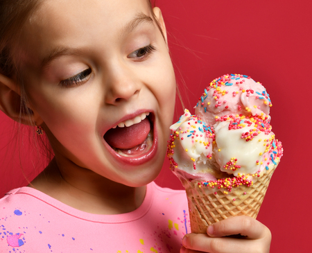 Pretty baby girl kid eating licking big ice cream in waffles cone with raspberry happy laughing on red background Archivio Fotografico
