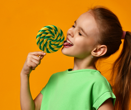 Happy young little child girl kid lick sweet lollypop candy on yellow background Stock Photo