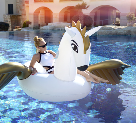 Young fashion woman relaxing in luxury swimming pool resort hotel on big inflatable unicorn pegasus float mattress in white bikini