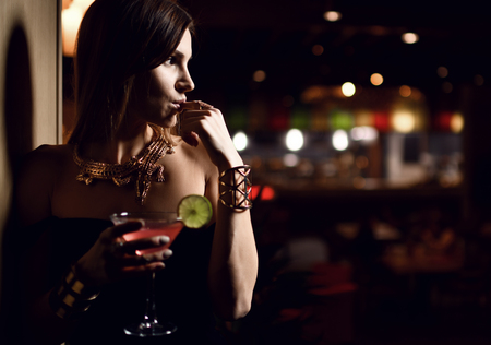 Beautiful sexy fashion brunette woman in expensive interior restaurant drink martini cosmopolitan cocktail on dark cafe background Stock Photo