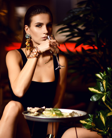 Beautiful sexy fashion brunette woman in expensive interior restaurant eat oyster and drink champagne on dark cafe background