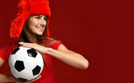Russian style fan sport woman player in red uniform and ear-flap hat hold soccer ball celebrating happy smiling looking at the corner on red background Stock Photo