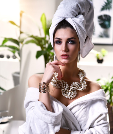 Young beautiful woman with white towel on head looking at the mirror wearing bathrobe and gold pearl jewellery in modern bathroom with plants