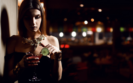 Beautiful fashion brunette woman in expensive interior restaurant relaxing with martini cosmopolitan cocktail in big chair on dark cafe background