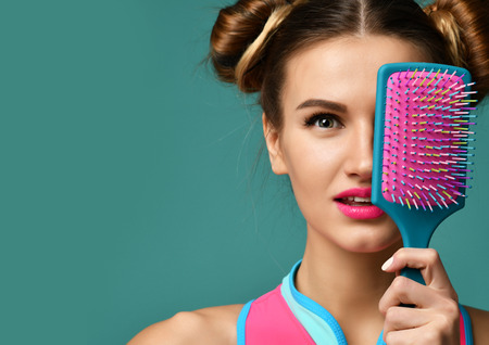 Closeup portrait of happy fashion brunette woman close eyes with colorful pink blue big hair comb brush on modern mint background