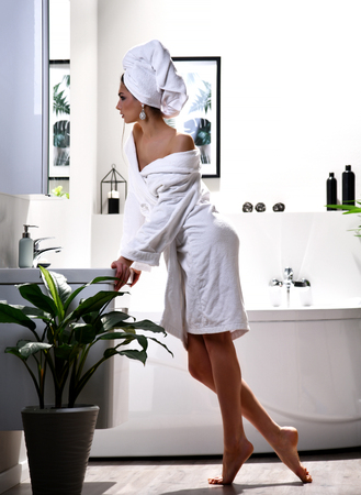 Young beautiful woman with white towel on head do makeup looking at the mirror wearing bathrobe in modern bathroom with plants Stock Photo