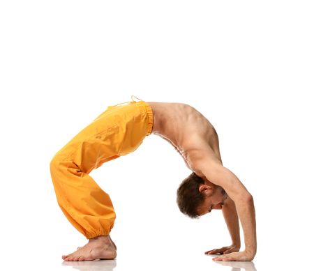 Man practicing yoga doing sport stretching exercises in yellow pants isolated on white background