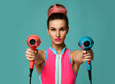 Happy young brunette woman with hair dryer on blue mint background. Hair style beauty concept
