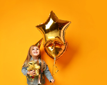 Three years girl toddler kid with gold presents balloons and birthday cap celebrating on yellow background