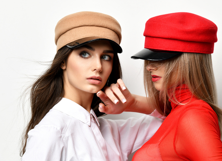 Two young fashion brunette woman in red and brown peaked cap together on grey background