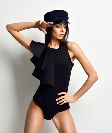 Young sexy brunette woman in fashion black vest and peaked cap or beret on grey background Stock fotó