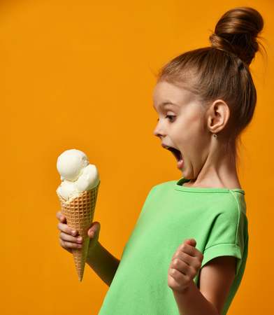 Pretty baby girl kid eating licking banana and vanilla ice cream in waffles cone on yellow background with free text copy space