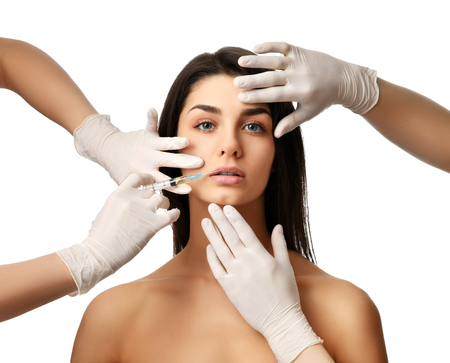Lips cosmetology plastic surgery beauty concept young brunette woman face and  doctor hand in glove with syringe making injection Stock Photo