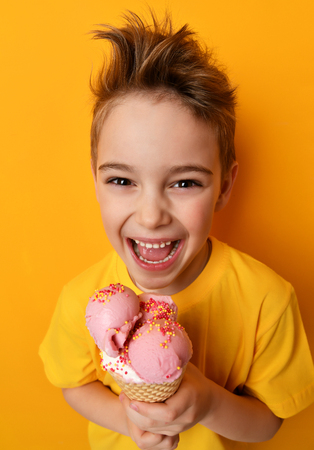 Baby boy kid eating strawberry ice cream in waffles cone happy smiling laughing on yellow background with free text copy space
