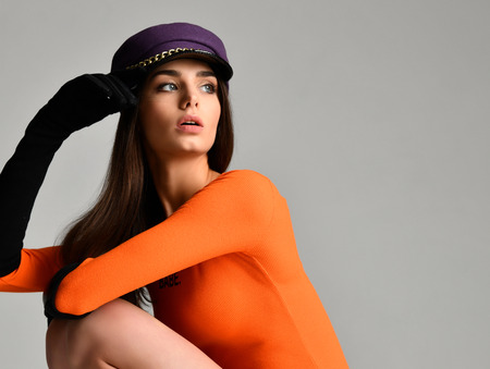 Young brunette woman in purple peaked cap beret in black gloves and orange blouse sitting and looking at the corner on gray background