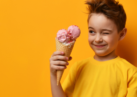 Baby boy kid eating strawberry ice cream in waffles cone and winking on yellow background with free text copy space