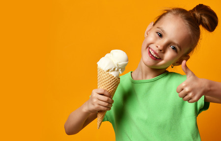 Pretty baby girl kid eating licking vanilla ice cream in waffles cone on yellow background Reklamní fotografie