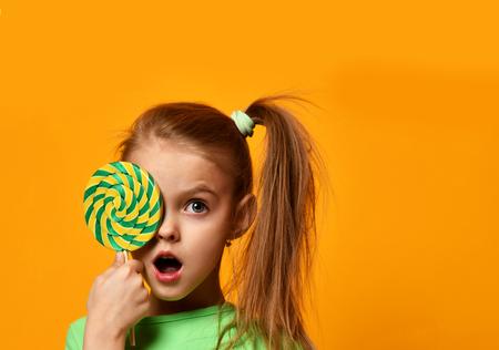 Glückliches junges kleines Kind Mädchen Kind beißen süße Süßigkeiten Süßigkeiten auf gelbem Hintergrund