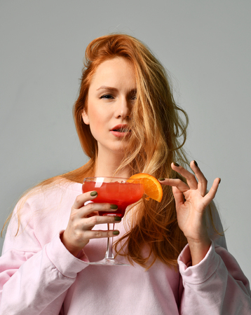 Bartender woman with red strawberry cosmopolitan margarita cocktail in hand on gray background Stock Photo