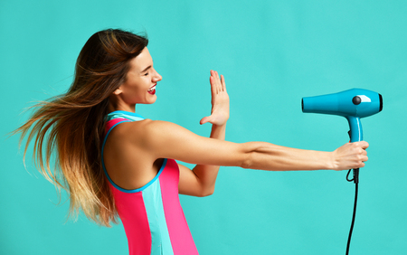 Happy young brunette woman pointing hair dryer on blue mint background. Hair style beauty concept Stockfoto