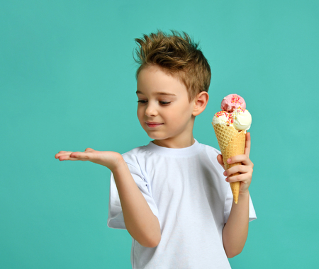 Baby boy kid hold strawberry ice cream in waffles cone on blue mint background with free text copy space