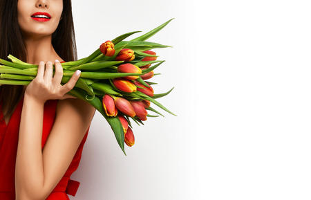 Beautiful woman with bouquet of tulip flowers in red dress and looking at the corner with empty text copy space on gray background