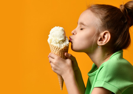 Pretty baby girl kid kiss vanilla ice cream in waffles cone on yellow background and show thumbs up sign with free text copy space