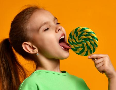 Szczęśliwe młode małe dziecko dziewczynka dzieciak ugryźć słodkie lollypop cukierki na żółtym tle