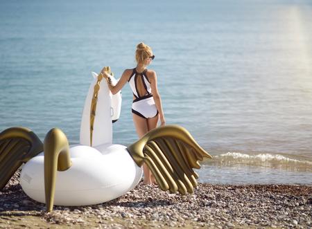 Young pretty fashion woman standing on sea shore beach near resort hotel with giant inflatable unicorn pegasus float mattress in white bikini