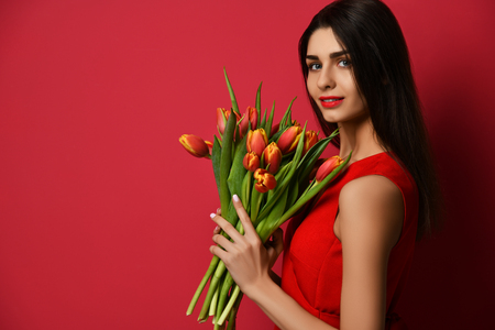 Beautiful woman with bouquet of tulip flowers in red dress and looking at the corner with empty text copy space on dark pink background Stock Photo