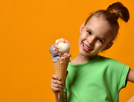 Pretty baby girl kid eating licking vanilla ice cream in waffles cone on yellow background 写真素材