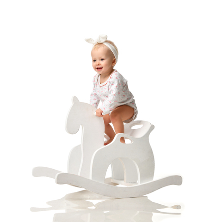 Toddler baby girl is riding swinging on a rocking chair toy horse over white background Standard-Bild
