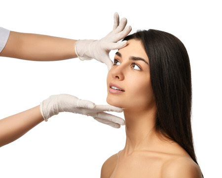 Doctor hands in medical gloves touch beautiful young woman face with closed eyes after plastic surgery isolated on white background