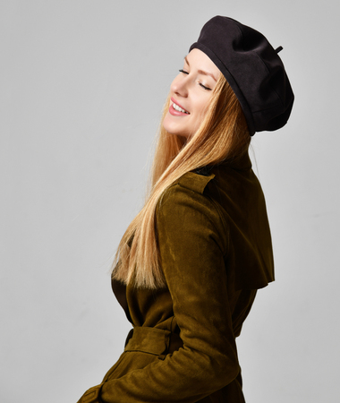 Young sexy brunette woman in dark brown beret hat and spring jacket coat looking at the corner on gray background