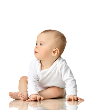7 month infant child baby  girl toddler sitting in white shirt looking at the corner isolated on a white background