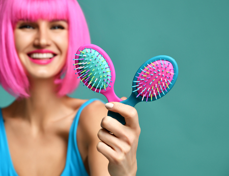 Closeup portrait of happy fashion brunette woman hold two small pink blue yellow small hair comb brush in pink wig on modern mint background