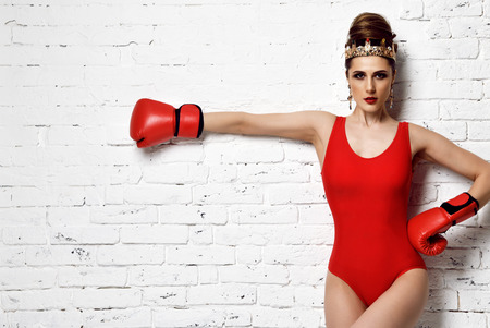 Beautiful glamour sexy woman with red Boxing Gloves and fashion gold crown and earrings on brick wall background