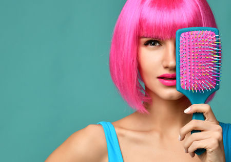 Closeup portrait of happy fashion brunette woman close mouth with colorful pink blue yellow small hair comb brush in pink wig on modern mint background