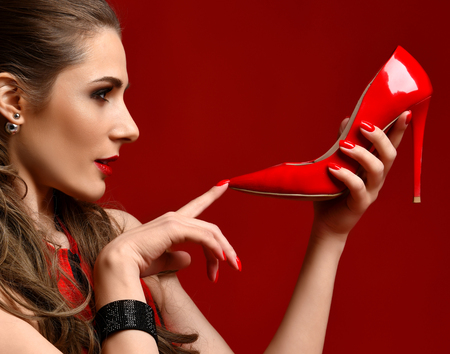 Beautiful brunette woman hold red shoe high hill on dark red background