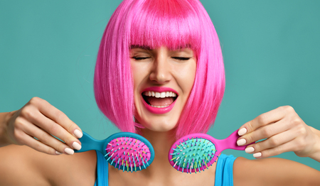 Closeup portrait of happy fashion brunette woman hold two small pink blue yellow small hair comb brush laughing in pink wig on modern mint background