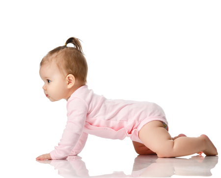 8 month infant child baby girl toddler learning how to crawl in pink shirt looking at corner isolated on a white background Stock Photo