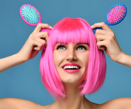 Closeup portrait of happy fashion brunette woman hold two small pink blue yellow small hair comb brushes looking up in pink wig on blue background Archivio Fotografico