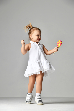 Young pretty toddler girl kid with big  sweet lollypop candy in white dress on grey background