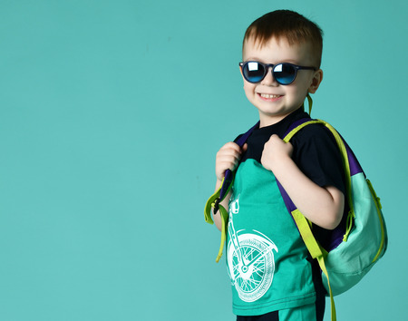 Preschool boy kid standing with backpack and sunglasses in shorts and t-shirt on green mint background Banco de Imagens