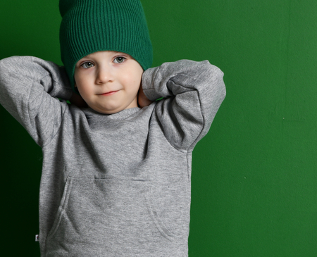 Preschool boy kid standing in gray hoodie sweater and winter hat on green mint background