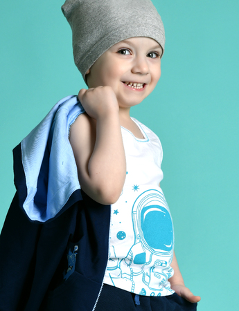 Preschool boy kid standing in blue hoodie and gray hat in shorts and t-shirt happy on green mint background Imagens