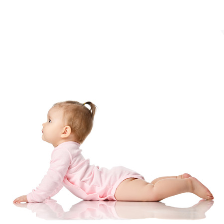 8 month infant child baby girl toddler lying in pink shirt looking at corner isolated on a white background Stock Photo