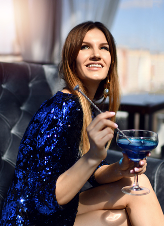 Beautiful sexy fashion brunette woman sitting in expensive interior restaurant drinking drinking blue margarita cocktail looking at the corner